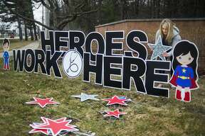 """Morgan Jackson, owner of Sign Gypsies Mid Michigan, installs a sign honoring hospital workers at the Saginaw Road entrance for MidMichigan Medical Center - Midland Monday, March 30, 2020. Jackson donated the sign, which reads """"Heroes work here,"""" to thank hospital staff for their hard work and long hours during the coronavirus pandemic. (Katy Kildee/kkildee@mdn.net)"""