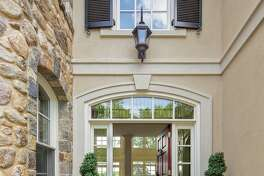 The arched front entrance is capped with a keystone and the door is framed by sidelights and a multi-paned arched transom.