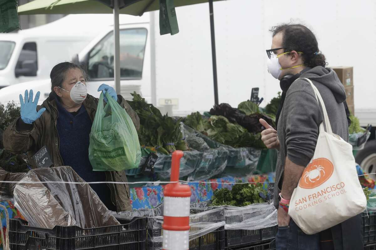 Annabelle Lenderink, left, wears a mask while helping customer Justin Angel at the Star Route Farms stand at the Ferry Plaza Farmers Market in San Francisco, Saturday, March 28, 2020.