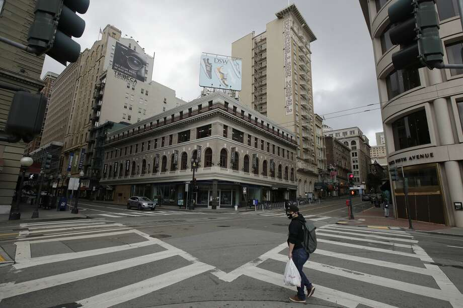 A man wears a mask while crossing an empty intersection in the Union Square retail area of San Francisco, Sunday, March 29, 2020. Californians endured a weekend of stepped-up restrictions aimed at keeping them home as much as possible while hospitals and health officials scrambled Sunday to ready themselves for a week that could see the feared dramatic surge in coronavirus cases. Photo: Jeff Chiu/Associated Press / Copyright 2020 The Associated Press. All rights reserved