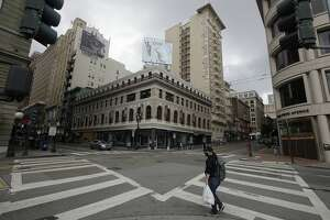 A man wears a mask while crossing an empty intersection in the Union Square retail area of San Francisco, Sunday, March 29, 2020. Californians endured a weekend of stepped-up restrictions aimed at keeping them home as much as possible while hospitals and health officials scrambled Sunday to ready themselves for a week that could see the feared dramatic surge in coronavirus cases.