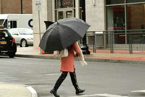 A pedestrian uses an umbrella in the rain as she walks down New Scotland Ave. on Monday, March 30, 2020 in Albany, N.Y. (Lori Van Buren/Times Union)