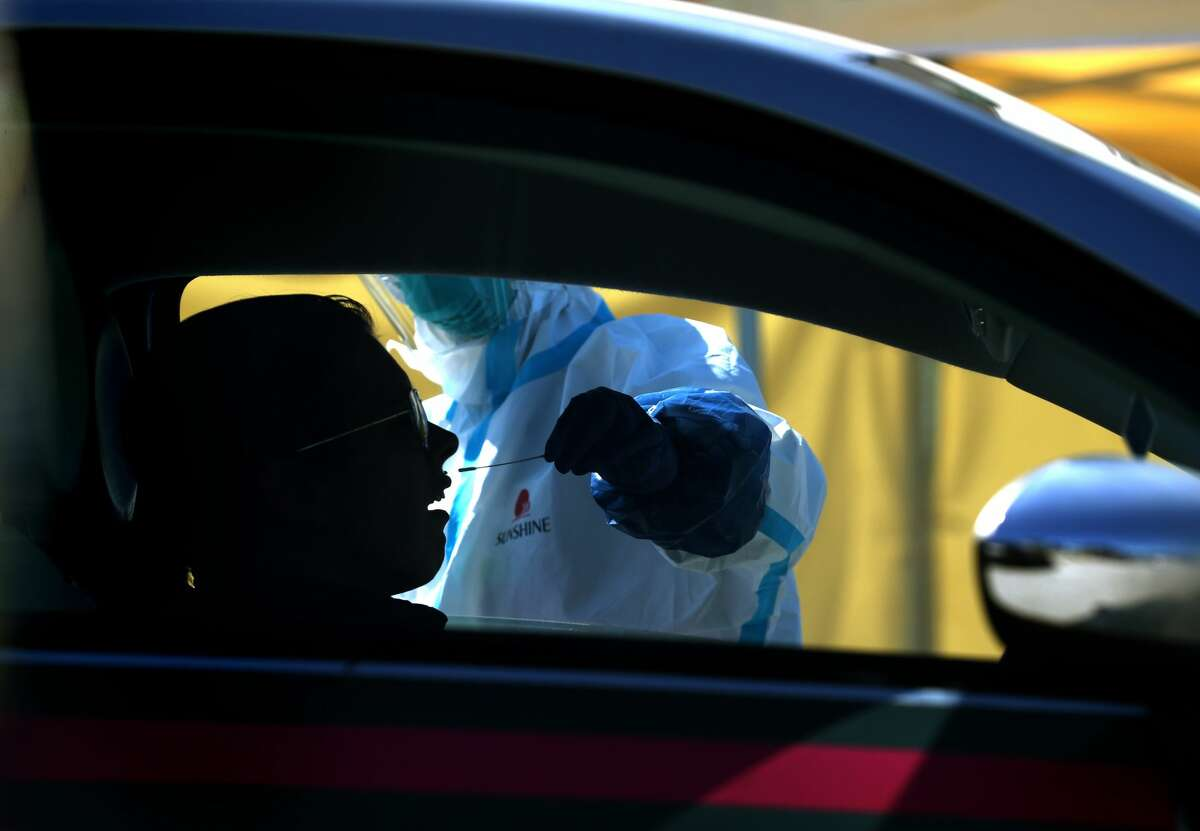 A medical professional administers a coronavirus (COVID-19) test during a drive-thru testing station on March 26, 2020 in Daly City, California. New coronavirus testing stations are opening up each day in the San Francisco Bay Area.
