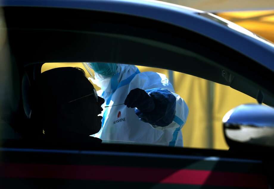 A medical professional administers a coronavirus (COVID-19) test during a drive-thru testing station on March 26, 2020 in Daly City, California. Photo: Justin Sullivan/Getty Images / 2020 Getty Images