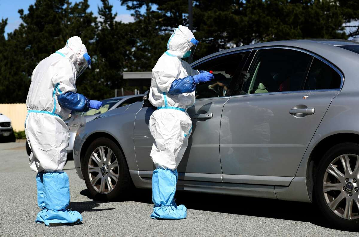 Medical professionals administer a coronavirus (COVID-19) test during a drive-thru testing station on March 26, 2020 in Daly City, California. New coronavirus testing stations are opening up each day in the San Francisco Bay Area.
