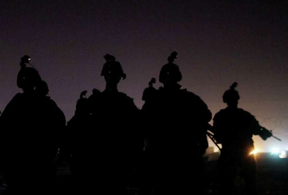 In this Aug. 15, 2010 photo, U.S. Army soldiers from C Co., 4th Battalion, 9th Infantry Regiment, 2nd Infantry Division gather for inspection of their night-vision and equipment before driving from Iraq to Kuwait. The soldiers are the last combat brigade to leave Iraq as part of the drawdown of U.S. forces. (AP Photo/ Maya Alleruzzo) Photo: Maya Alleruzzo, ASSOCIATED PRESS / AP 2010