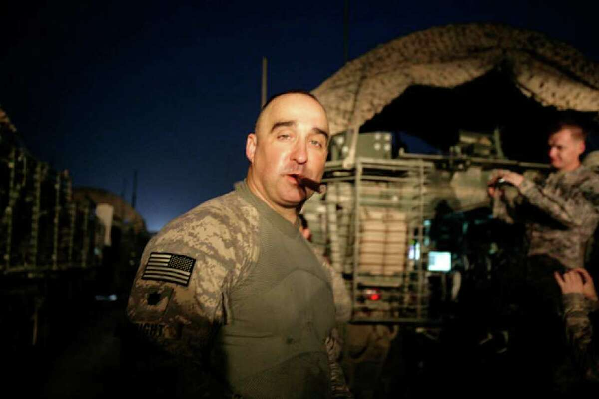In this Aug. 16, 2010 photo, U.S. Army Lt. Col. Darron Wright, deputy commander, 4th Brigade, 2nd Infantry Division, smokes a cigar after crossing the border from Iraq into Kuwait, more than seven years after he drove into Iraq during the US invasion. Lt. Col Wright, from Mesquite, Texas, is the deputy commander of the last combat brigade to leave Iraq as part of the drawdown of U.S. forces. (AP Photo/ Maya Alleruzzo)