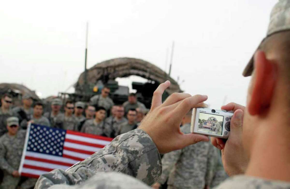 In this Aug. 16, 2010 photo, U.S. Army soldiers from 4th Battalion, 9th Infantry Regiment pose with an American flag for a photograph after crossing the border from Iraq into Kuwait. The soldiers from 4th Brigade, 2nd Infantry Division, are the last combat brigade to leave Iraq as part of the drawdown of U.S. forces. (AP Photo/ Maya Alleruzzo)