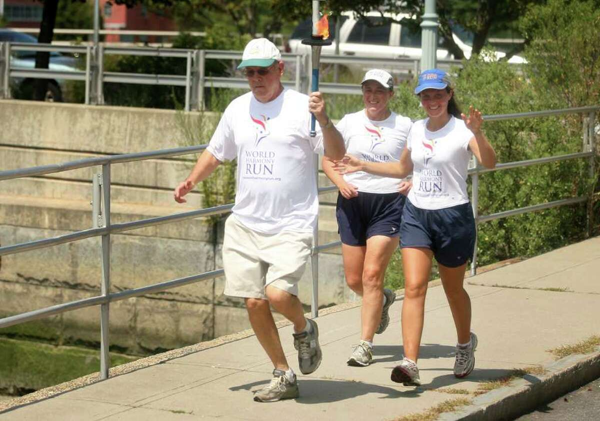 From left; Bill Hass, president of the U.N. Association of Southwest Connecticut, carries the torch through downtown Westport alongside World Harmony runners Kukila Chamberlain of England and Surya Smolennikova of Russia as part of the 10,00 mile World Harmony Run USA. The run began on April 18 in New York City and has passed through over 1,000 cities and towns this summer.