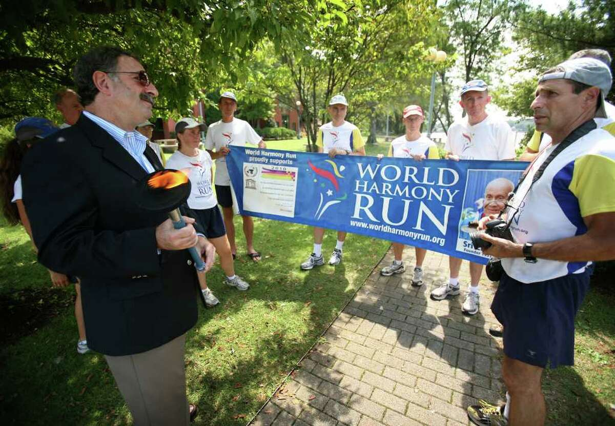 RTM member Jonathan Steinberg greets the running team from the World Harmony Run during their stop in Westport on Tuesday, August 17. The 10,000 mile torch run, which began in New York City on April 18, passed though over 1,000 cities and towns this summer.