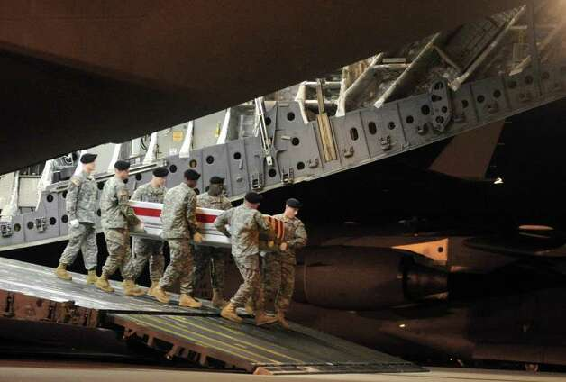 An Army carry team Thursday carries a transfer case containing the remains of Staff Sgt. Derek J. Farley at Dover Air Force Base, Del. (Steve Ruark / Associated Press)