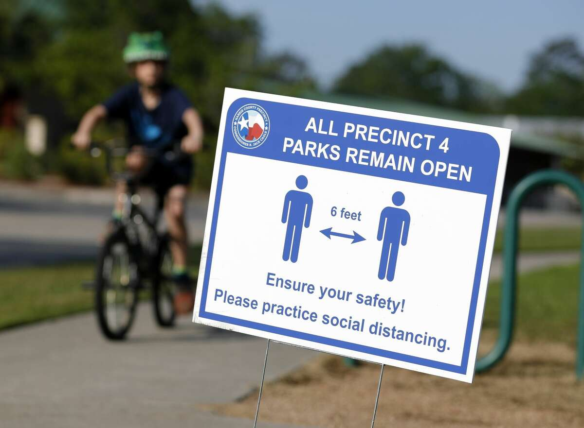 A sign reminds visitors at Dennis Johnston Park to practice social distancing, Thursday, March 27, 2020.