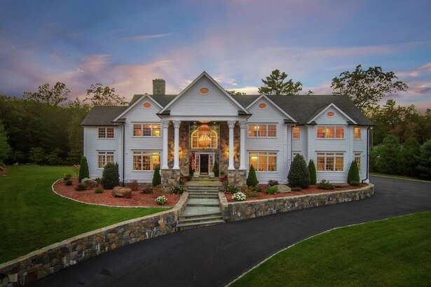 The 8,248-square-foot stone and white clapboard colonial house at 125 Judd Road sits on a 3.19 level and gently sloping estate.