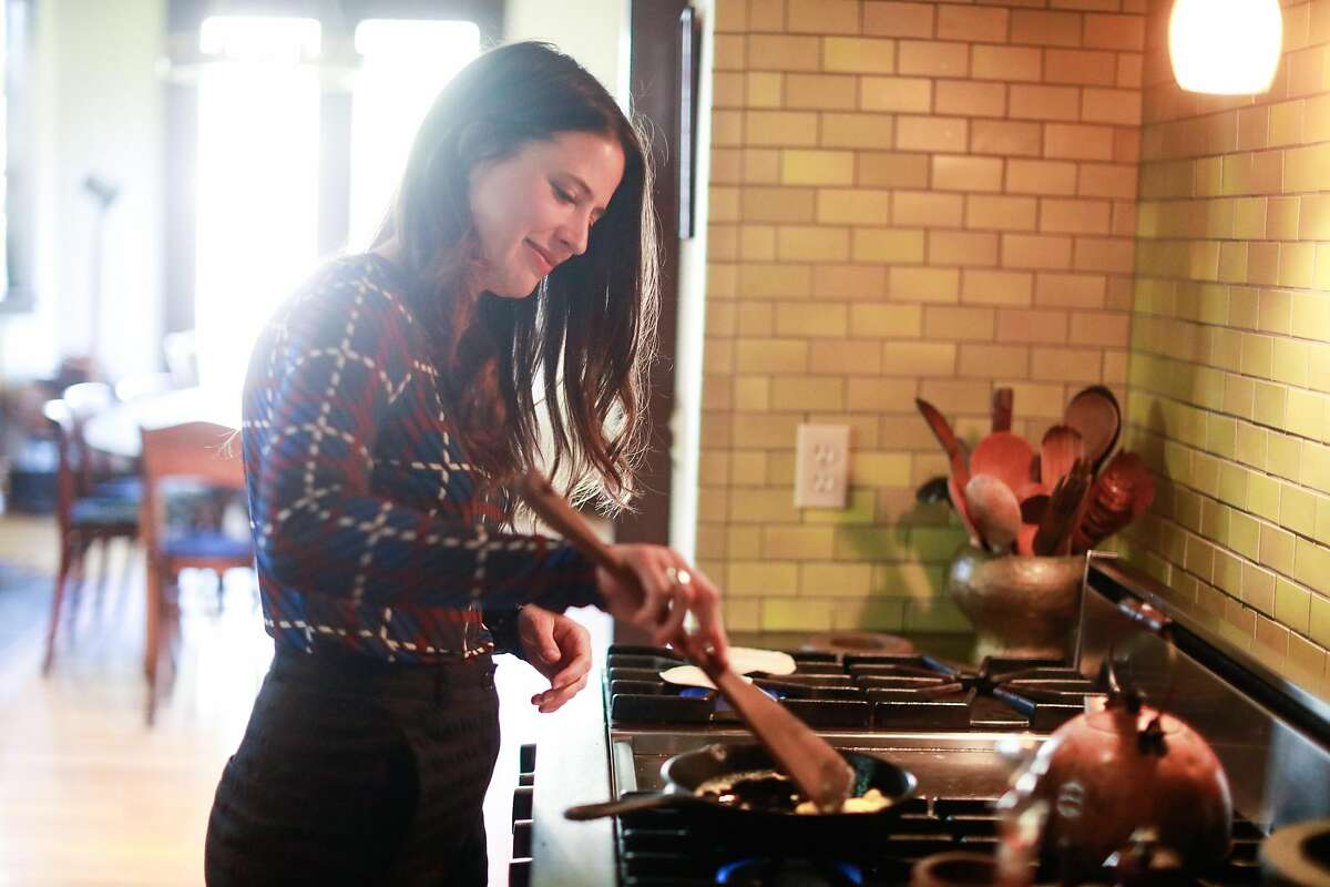 Fanny Singer, the daughter of Alice Waters, prepares a snack for a friend at her childhood home in Berkeley, California on Monday, March 2, 2020. Singer�s new memoir which features recipes from her childhood titled �Always Home: A Daughter's Recipes & Stories� will be released later this month.