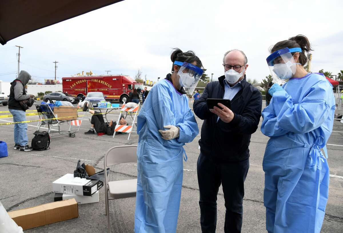 Touro University Nevada medical school Dean Dr. Wolfgang Gilliar (C) talks with Touro medical students Claire Chen (L) and Allison Moran (R) as they wait to conduct medical screenings as people line up to enter a temporary homeless shelter set up in a parking lot at Cashman Center on March 28, 2020 in Las Vegas, Nevada. Catholic Charities of Southern Nevada was closed this week after a homeless man who used their services tested positive for the coronavirus, leaving about 500 people with no overnight shelter. The city of Las Vegas, Clark County and local homeless providers plan to operate the shelter through April 3rd when it is anticipated that the Catholic Charities facility will be back open. The city is also reserving the building spaces at Cashman Center in case of an overflow of hospital patients.
