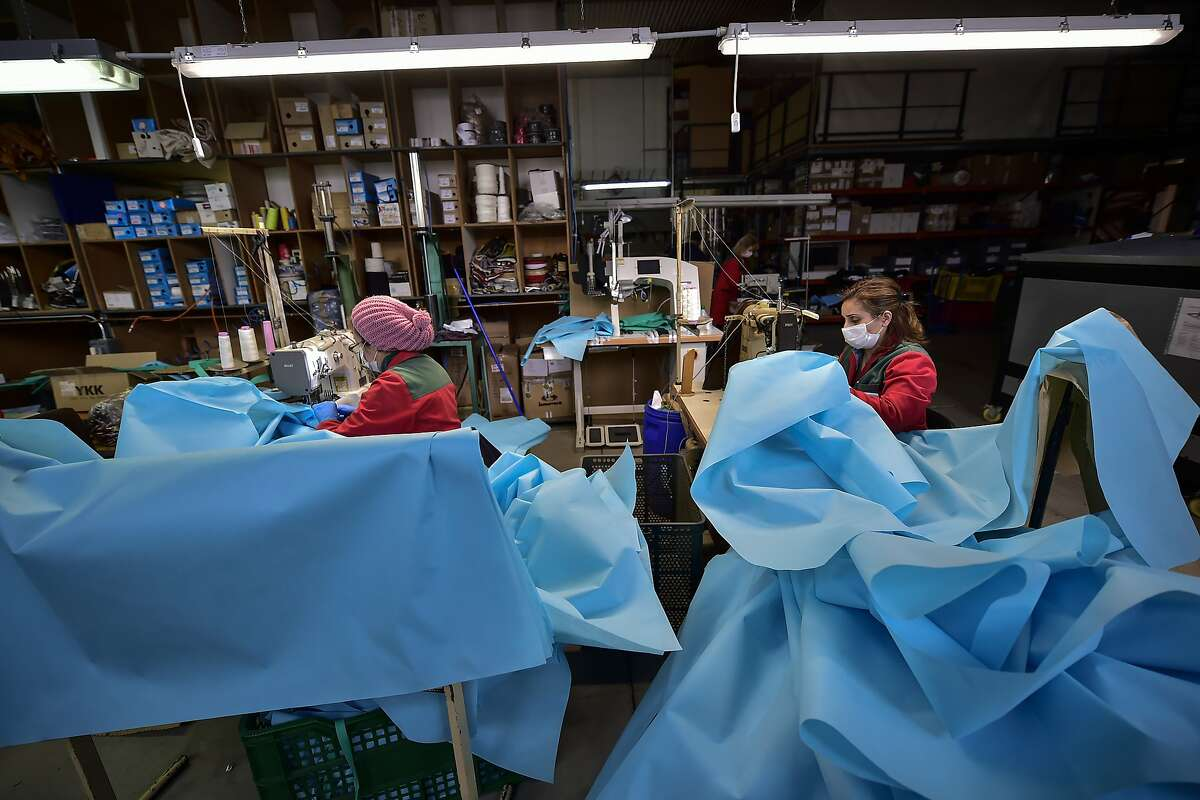 Volunteer workers in a clothing factory manufacturing firefighting gear, make hospital gowns for medical staff to protect them from the coronavirus, in Arnedo, northern Spain, Monday, March 30, 2020. The new coronavirus causes mild or moderate symptoms for most people, but for some, especially older adults and people with existing health problems, it can cause more severe illness or death. (AP Photo/Alvaro Barrientos)