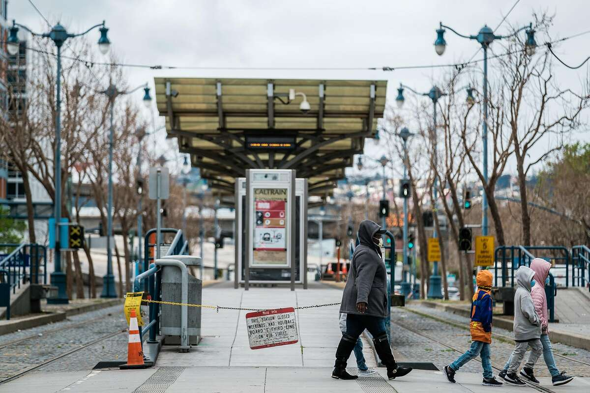 Pedestrians walk past the closed Muni station at 4th and King St. in San Francisco, Calif. on Monday March 30, 2020.