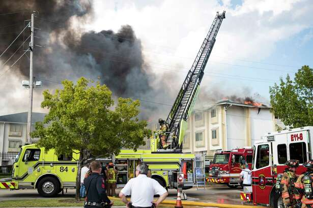 Firefighters from Spring, Ponderosa, Little York, Klein, and The Woodlands Fire Departments battle a multi-alarm fire at the Motel 6 on Cypresswood CT in North Harris County Wednesday, Oct 9, 2019, in Houston.