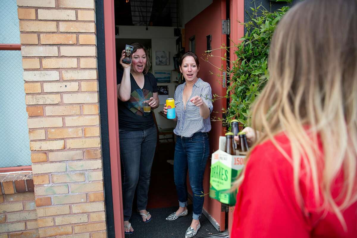 """Rebecca Kelly, a currently out of work bartender and volunteer delivery driver for Kon-Tiki, brings a delivery to Megan Hughes (center) and Kimber Oswald while they have a """"FaceTime Happy Hour"""" with their friend Jess Warshaver in Oakland, Calif. on Friday, March 20, 2020. Starting Friday evening the Kon-Tiki Bar with be offering deliveries to Oakland residents of mixed drinks bottled at the restaurant, including the House Zombie, The Kon-Tiki Grog, Virgin's Sacrifice, Man Tai and a 22 oz. Ma Kua for two. The ABC has relaxed regulations for bars and restaurants during shelter in place, allowing them to now offer cocktail deliveries and drive-through options for alcohol."""