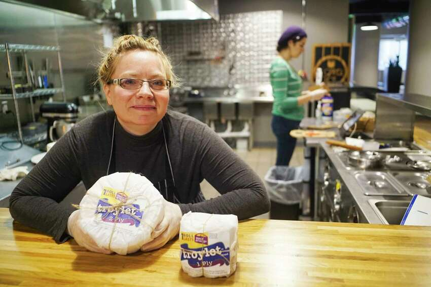 Susan Dunckel, owner of Sweet Sue's Copper Pot, holds the six inch round pound cake, the 2-ply, with the four inch round cake, the 1-ply, seen on the counter on Monday, March 30, 2020, in Troy, N.Y. Dunckel began selling the cakes decorated to look like a roll of toilet paper on Saturday and Monday was the first day she began filling all the orders. Becky Kendall, background, a recruited baker that Dunckel has brought in to help fill the orders. (Paul Buckowski/Times Union)