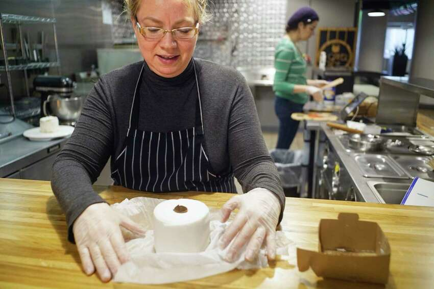 Susan Dunckel, owner of Sweet Sue's Copper Pot, unwraps the four inch round pound cake, the 1-ply, on Monday, March 30, 2020, in Troy, N.Y. Dunckel began selling the cakes made to look like a roll of toilet paper on Saturday and Monday was the first day she began filling all the orders. Becky Kendall, background, a recruited baker that Dunckel has brought in to help fill the orders. (Paul Buckowski/Times Union)