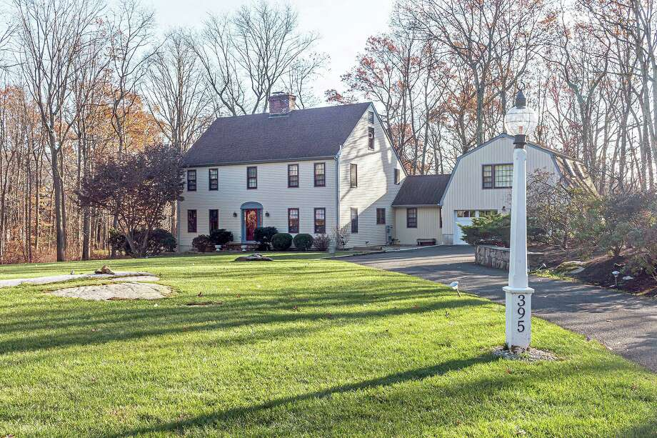 The beige colonial house at 395 Thayer Pond Road in South Wilton sits on a level corner lot of two acres. Photo: SUE FERGUSON