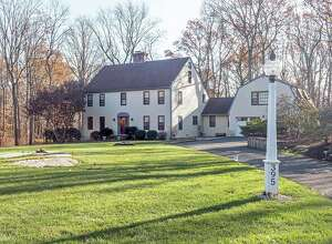 The beige colonial house at 395 Thayer Pond Road in South Wilton sits on a level corner lot of two acres.