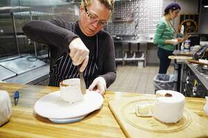 Susan Dunckel, owner of Sweet Sue's Copper Pot, applies a vanilla buttercream icing to a four inch round pound cake on Monday, March 30, 2020, in Troy, N.Y. Dunckel began selling the cakes made to look like a roll of toilet paper on Saturday and Monday was the first day she began filling all the orders. Becky Kendall, background, a recruited baker that Dunckel has brought in to help fill the orders.   (Paul Buckowski/Times Union)