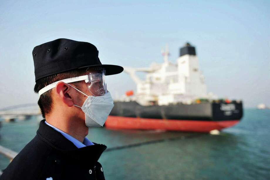 A police officer wearing a mask amid concerns over the COVID-19 coronavirus while keeping watch as a Kuwaiti oil tanker unloads crude oil at the port in Qingdao, in China's eastern Shandong province. Photo: STR,  Contributor / AFP Via Getty Images / AFP or licensors
