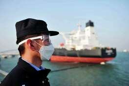 A police officer wearing a mask amid concerns over the COVID-19 coronavirus while keeping watch as a Kuwaiti oil tanker unloads crude oil at the port in Qingdao, in China's eastern Shandong province.