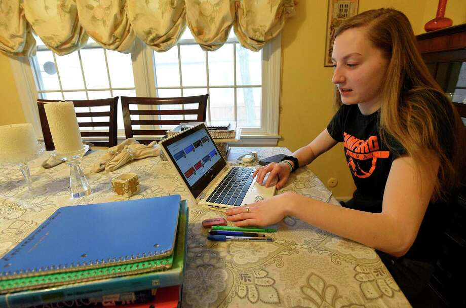 Megan Landsiedel, a senior at Stamford High School, sits with her books at her home in Stamford, Connecticut on March 17, 2020. Landsiedel uses her laptop to complete classroom instruction set up by her teachers as part of the school's virtual learning environment and uses Social Media to stay in touch with her friends to collaborate on school projects. Each day, student's are task with completing assignments, while schools remain closed in response to the COVID-19 pandemic. Photo: Matthew Brown / Hearst Connecticut Media / Stamford Advocate