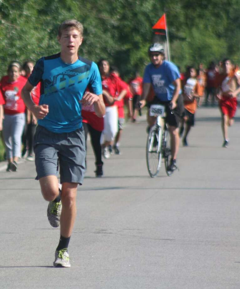 """Although his Get Fit Jog career was over, First Team All-Decade selection Benjamin Stereff plays the role of the """"rabbit,"""" leading some GFJ runners towards the football stadium and the finish line. Photo: Robert Avery"""