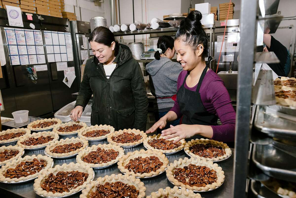 Owner Lenore Estrada, left, checks in on Bourbon Pecan pies being made by Julie Tran at Three Babes Bakeshop in San Francisco, California, on Friday, March 6, 2020. Three Babes Bakeshop, which largely caters to local San Francisco tech employers, is seeing a dramatic decrease in business since tech companies are having employees work from home due to fears over the Coronavirus, and is having to make cutbacks in their production numbers and potentially may have to cut some workers' hours.