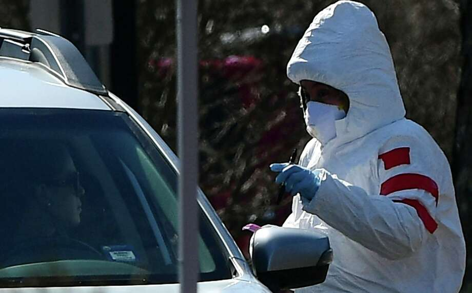 Workers with Murphy Medical Associates conduct corona virus at a drive-thru testing station Tuesday, March 24, 2020, at Bedford Middle School in Westport, Conn. Due to a large coronavirus outbreak in Westport, the Westport Weston Health District arranged for additional community testing. Residents of Westport and Weston were tested by Murphy Medical Associates, a private company, from 8:30 a.m. to noon. Photo: Erik Trautmann / Hearst Connecticut Media / Norwalk Hour