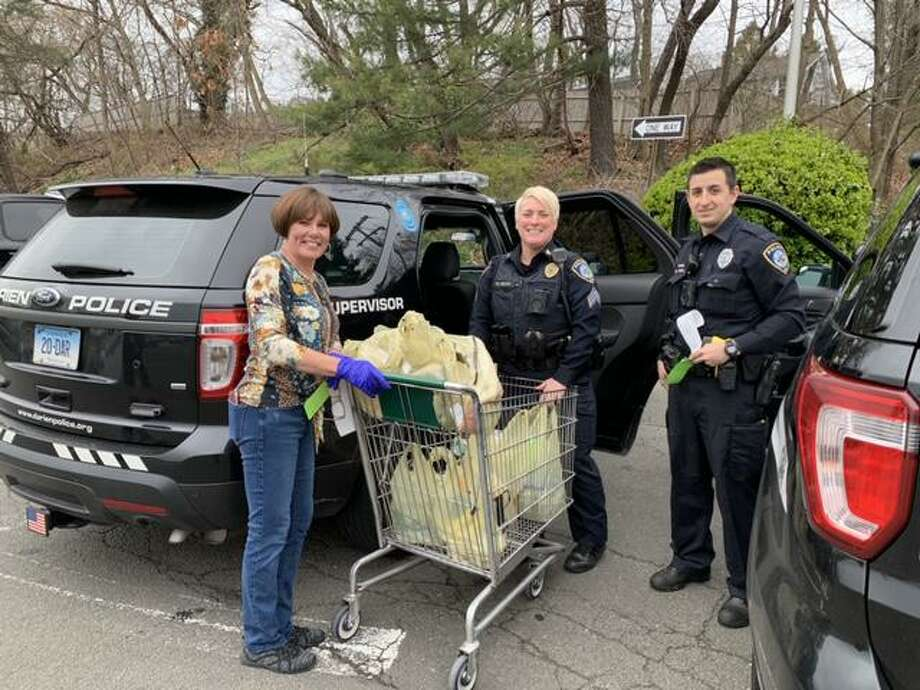 Cindy Palmer, Sgt. Keri Isaac and Officer Chris Jimenez as the members of the Darien Police Department pick up bags of groceries to deliver. Photo: Willow Buscemi /Contributed Photo