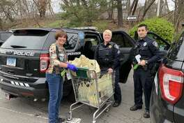 Cindy Palmer, Sgt. Keri Isaac and Officer Chris Jimenez as the members of the Darien Police Department pick up bags of groceries to deliver.