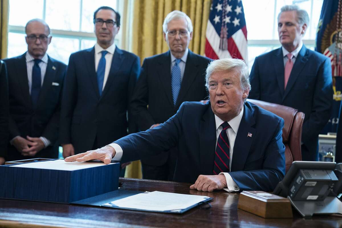 President Donald Trump talks to reporters before signing the coronavirus stimulus relief package in the Oval Office at the White House, Friday, March 27, 2020, in Washington, as White House chief economic adviser Larry Kudlow, Treasury Secretary Steven Mnuchin, Senate Majority Leader Mitch McConnell, R-Ky., and House Minority Leader Kevin McCarty, R-Calif. (AP Photo/Evan Vucci)