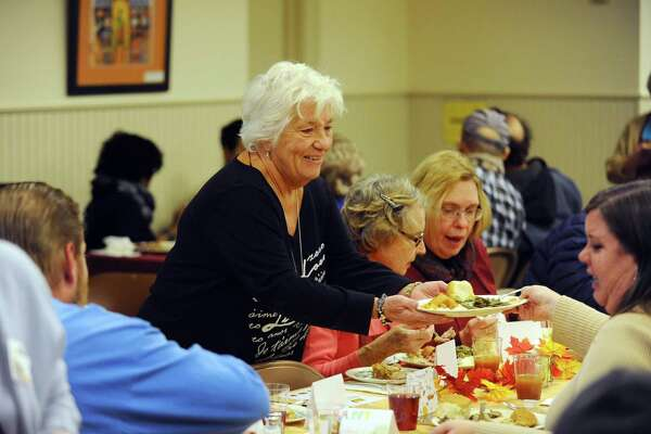 Marion McGarry, a member of the board of representatives for Stamford's 12th district, helps clear the table to make way for dessert during the First Congregational Church's Thanksgiving Day on Thursday, Nov. 24, 2016. McGarry died from cancer Sunday.