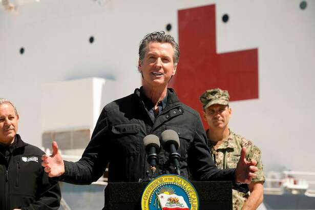 California Governor Gavin Newsom (C), flanked by Director Mark Ghilarducci, Cal OES, (L) and Admiral John Gumbleton, United States Navy, speaks in front of the hospital ship USNS Mercy after it arrived into the Port of Los Angeles on March 27, 2020. - The USNS Mercy, a giant US naval hospital ship, arrived in Los Angeles on March 27, where it will be used to ease the strain on the city's coronavirus-swamped emergency rooms. (Photo by Carolyn Cole / POOL / AFP) (Photo by CAROLYN COLE/POOL/AFP via Getty Images)