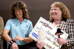 TIMES UNION PHOTO WILL WALDRON--Leanne Barrette, left, recives a $10,000 winners check from Bowlers Club owner------, in Latham. Barrette beat Wendy Macpherson to take the event. Sunday June 23, 2002.