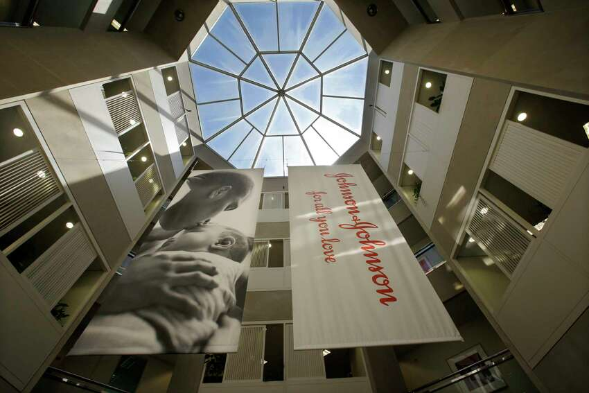 FILE - In this July 30, 2013, file photo, large banners hang in an atrium at the headquarters of Johnson & Johnson in New Brunswick, N.J. Johnson & Johnson has agreed to a $117 million multistate settlement over allegations it deceptively marketed its pelvic mesh products, which support women's sagging pelvic organs. (AP Photo/Mel Evans, File)