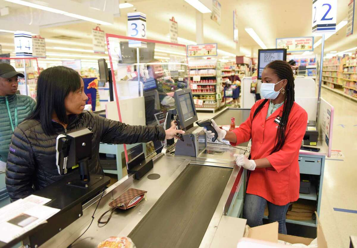 A cashier scans the phone of a shopper at ShopRite of Commerce St. in Stamford, Conn. Monday, March 30, 2020.