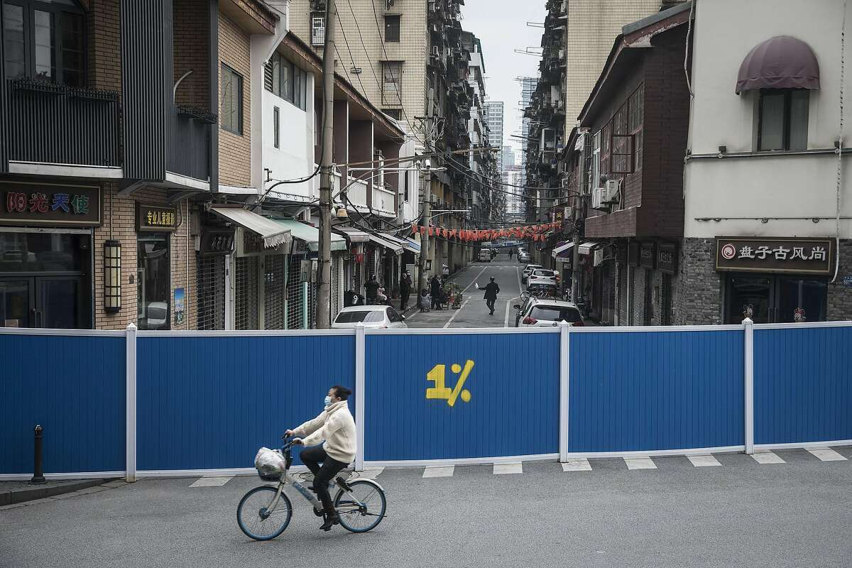 WUHAN, CHINA - MARCH 30: (CHINA OUT) A women on a bike rides past a makeshift barricade wall built to control entry and exit to a residential compound on March 30, 2020 in Hubei Province, China. Wuhan, the central Chinese city where the coronavirus (COVID-19) first emerged last year, will lift the lockdown on April 8, local media reported. (Photo by Getty Images)