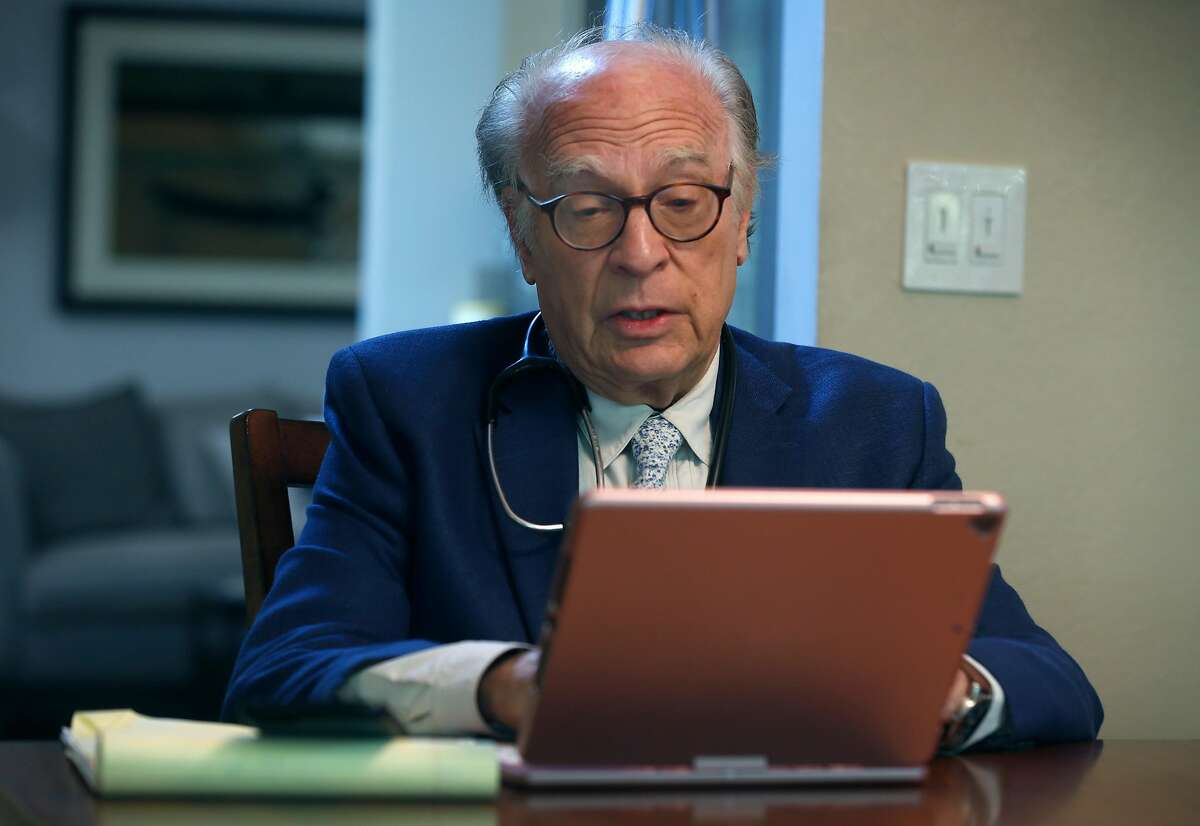 Dr. Neil Handelman meets with a patient remotely during a telemedicine appointment to discuss and diagnose possible coronavirus symptoms from his home in San Rafael, Calif. on Friday, March 27, 2020.