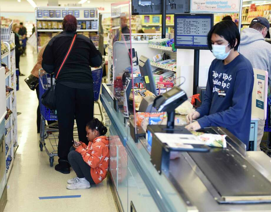 Greenwich's Ezell Pirtle, 6, plays a game while waiting behind a line of blue tape to check out with her motheras a sheet of plexiglass separates cashier Miguel Hernandez from customers in line at ShopRite of Commerce St. in Stamford, Conn. Monday, March 30, 2020. Many grocery stores are taking precautions in preventing the spread of coronavirus including signs promoting social distancing and plexiglass between shoppers and cashiers. Photo: Tyler Sizemore / Hearst Connecticut Media / Greenwich Time