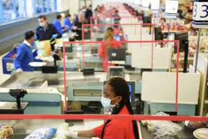 A sheet of plexiglass separates cashier Nadine Colas from customers in line at ShopRite of Commerce St. in Stamford, Conn. Monday, March 30, 2020. Many grocery stores are taking precautions in preventing the spread of coronavirus including signs promoting social distancing and plexiglass between shoppers and cashiers.