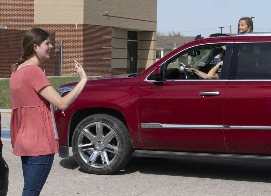 Hannah Killough waves as she and other Bowie Fine Arts teachers line the parking areas 03/30/2020 as parents drive their students around the school to say hi and encourage them. Tim Fischer/Reporter-Telegram Photo: Tim Fischer/Midland Reporter-Telegram