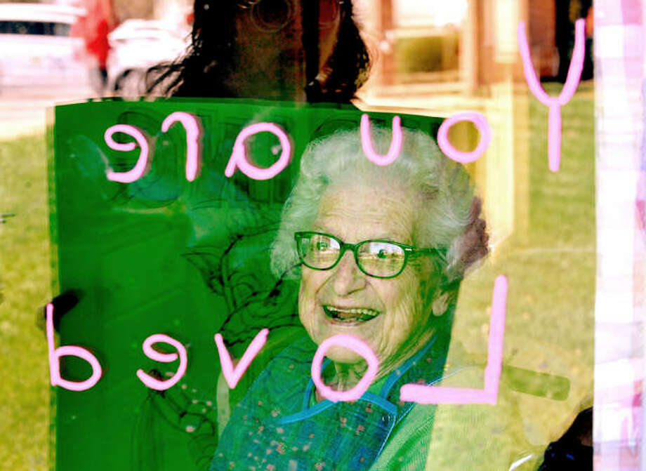 """Faye, a resident of Eden Village Retirement Community in Glen Carbon, looks through a message left on her window that says """"You are Loved"""" as a volunteer, reflected in the glass, holds a sign that displays more kind words. Photo: Photos By Thomas Turney 