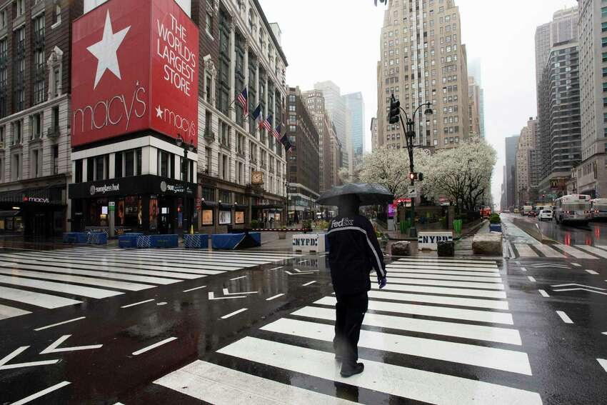 FILE - In this Monday, March 23, 2020 file photo, a man crosses the street in front of Macy's, in New York. Macy's is furloughing most of its 130,000 workers beginning this week as its sales have collapsed because of the coronavirus pandemic. The company said Monday, March 30 that it will be moving to an a€˜a€™absolute minimum workforce