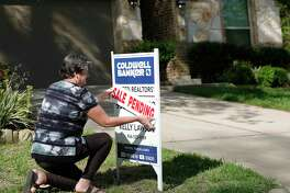 Relator Kelly Lawson attaches a sale pending sign in front of a home, Friday, March 27, 2020, in Willis.